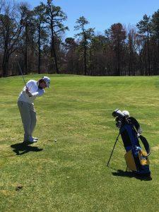 Brandon Mullarekey taking a swing on the golf course.