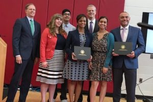 Marcy Vozella and Noemi Custodia-Lora accept the Early college designation from Gov. Baker.