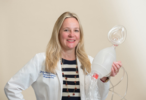 Jennifer Jackson Stevens holding a breathing device used in respiratory care.