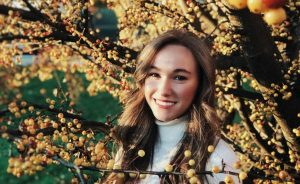 A portrait of Courtney Morin outside by a tree.