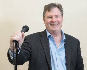 Dave Rattigan smiles with a mic stand in his hand