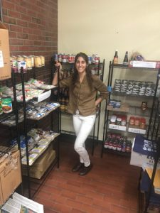 Elizabeth Mura stands next to shelving holding dry goods.