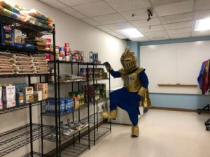NECC Knight mascot stands in the food closet looking at the dry goods.