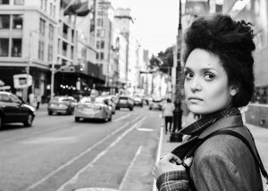Poet Diannely Antigua is in the forefront of a photograph taken on a busy city street.