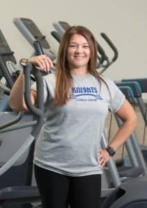 Amy Jacobs stands in the NECC Fitness Center surrounded by equipment.