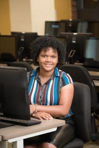 Kiara Santana Rosario sits at a computer in a computer classroom.