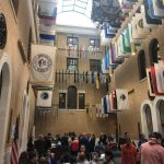 large atrium-style room with lots of windows and a flag hanging representing the 351 cities and towns in Massachusetts