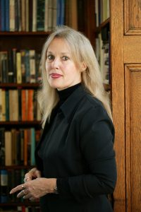 Elaine Scarry in all black with a bookcase behind her