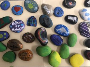 a batch of colorfully painted kindness rocks.