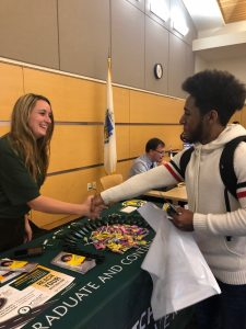 NECC student Joann Mejia shakes hands with representative from Fitchburg State University