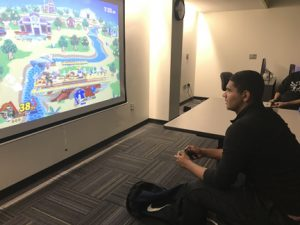 NECC student plays computer video game on projector