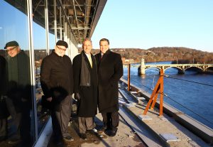 Three men stand at a railing overlooking the river.