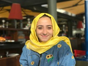 Amine Ekinci is smiling and wearing a yellow headscarf that matches the sunflowers on her denim jacket