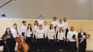 NECC Chorus students stand with black pants and white tops holding the selections of music to perform