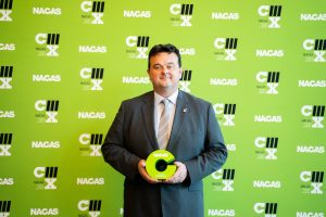 Mike McCarthy stands with a bright green award from National Association of College Auxiliary Services (NACAS)