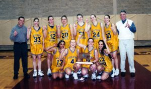 The members of the 2000-01 women's basketball team and their coaches pose for a celebratory photo.