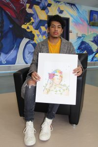 Kelvin Sabando sitting in a chair holding one of his watercolor paintings.