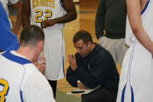 Stratton kneels with playbook among basketball players