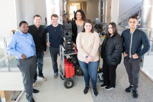 students and directors stand around camera equipment.