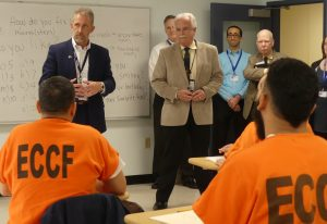 Two Essex County inmates wearing orange suits are in a classroom listening to NECC President Lane Glenn who is in front of the room with Essex County Sheriff Kevin Coppinger