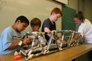 Four young children constructing a craft during College for Kids