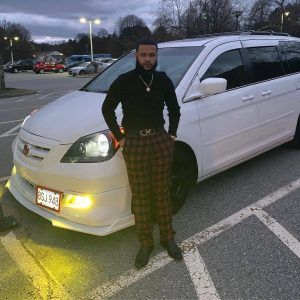 NECC graduate Jeurys Santiago standing in front of his car.