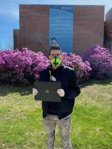 Man with face mask holds laptop computer.