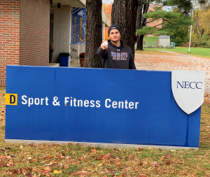 Student Athlete Mike Stellato standng in front of the NECC Sport a nd Fitness Center sign.