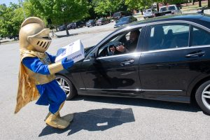 Knight mascot delivers package to NECC 2020 grad in car.