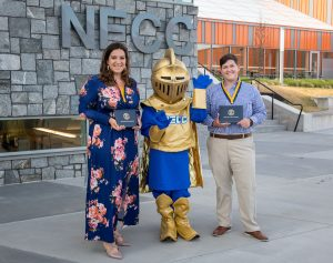 The NECC Knight mascot stands between two recently graduated women holding their diplomas.