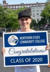 Young man in black cap holds yard sign for NECC Class of 2020
