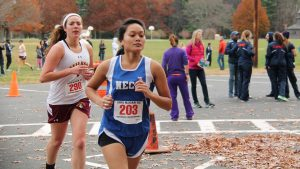 Two young woman participate in cross country running meet.