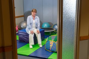 Woman sits in a colorful playroom