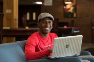 Young man in red shirt sits with laptop.
