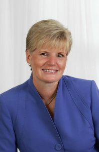 portrait of woman with short blonde hair wearing royal blue jacket.