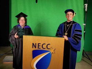 Man and woman holding award in academic regalia.