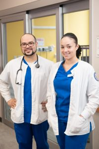 Two nursing students in white coats and scrubs.