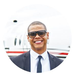 Young man wearing sunglasses and suit and tie.