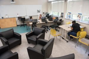 repurposed classroom with four comfortable chairs and desk with two people talking