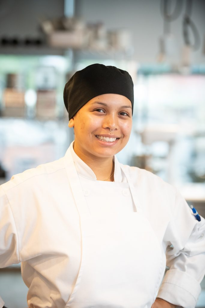image of culinary student Mercedes Rodriguez in chef's coat and apron, standing hands on hip smiling at the camera
