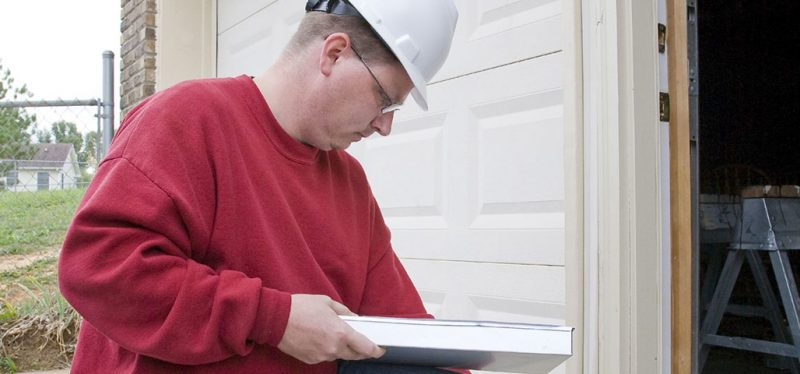 A home inspector wearing a helmet looks down at his paperwork as he enters a building under construction..
