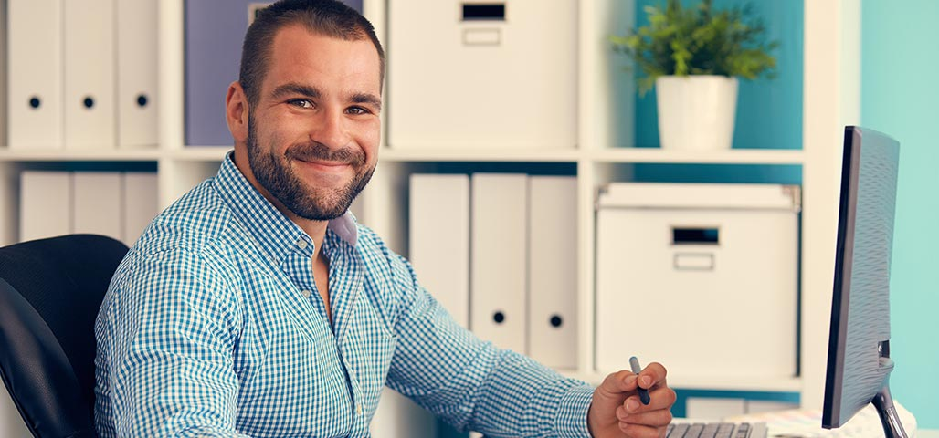 Smiling man sitting in front of computer in office setting.