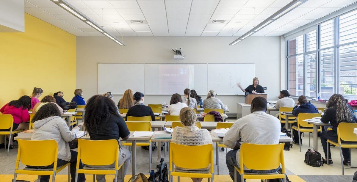 An Instructor at the front of a classroom talking to a room filled with students seated at desks .