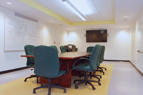 Room with a conference table nd chairs, flat screen mounted on   the far wall, and 2 large white boards on the left and right walls.