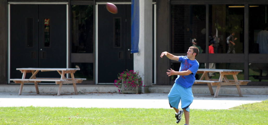 A student participating in one of the intramural student activies. He is throwing a football in front of the athletics building.
