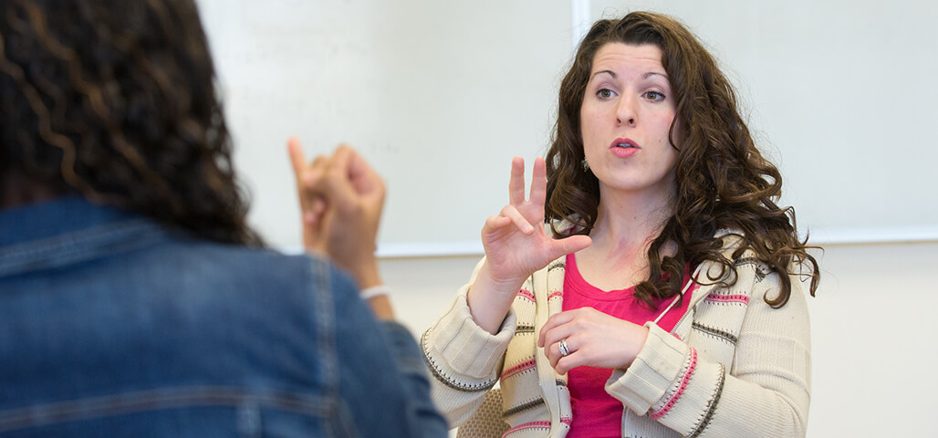 An American Sign Language Studies student signing to another person.