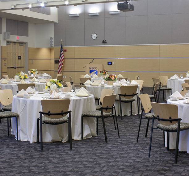 Round tables in the tech center with formal dinning settings; white floor length table clothes, and dinner settings on tables with wine glasses.