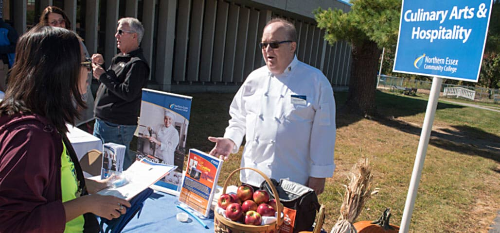 Dennis Boucher, program manager of the culinary arts cetificate program, conversing with a prospective student about the program at an open house.