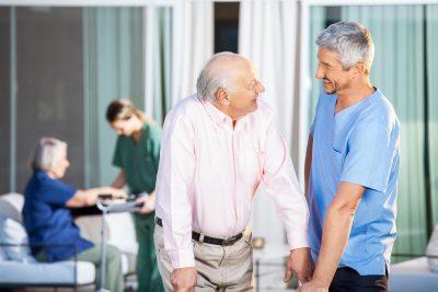 Happy male caretaker looking at disabled senior man at nursing home