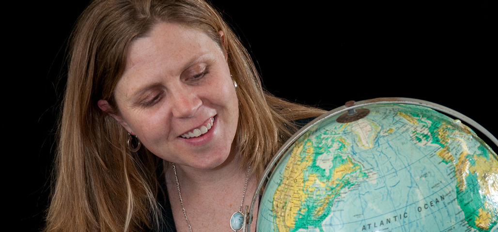 Professor Marcy Yeager, a speaker's bureau member, looking at a world globe
